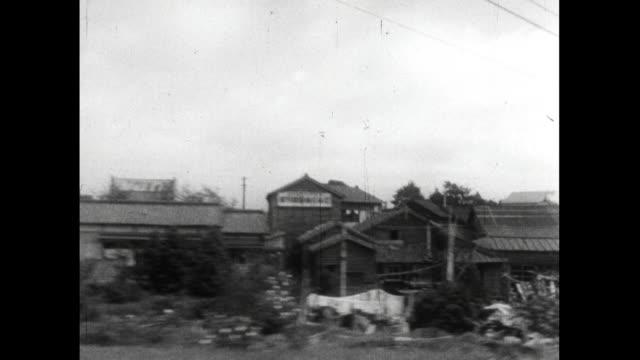pov from moving train of buildings beside tracks; japan, 1959 - 老朽化点の映像素材/bロール