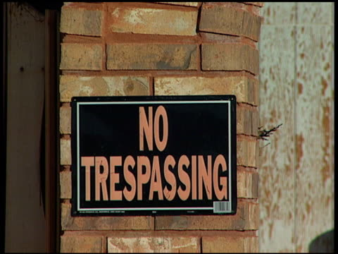 from one no trespassing sign on brick entrance way, to second no trespassing sign on other side of brick entrance way. home owner, housing crisis,... - no trespassing stock videos & royalty-free footage