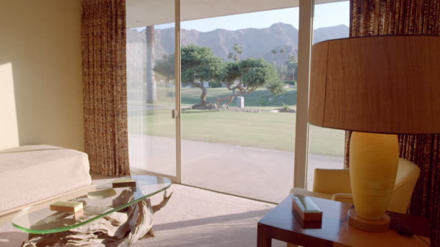 vídeos y material grabado en eventos de stock de ts from open glass slider door overlooking golf course to bedroom with two 1950s twin beds arranged at ninety degree angle - palace room