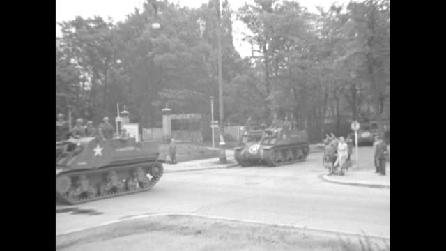 stockvideo's en b-roll-footage met from open turret of an american tank with soldiers at and guns at the ready / they drive past crowds of solemn, unmoving germans / the sleeve of a... - tweede wereldoorlog