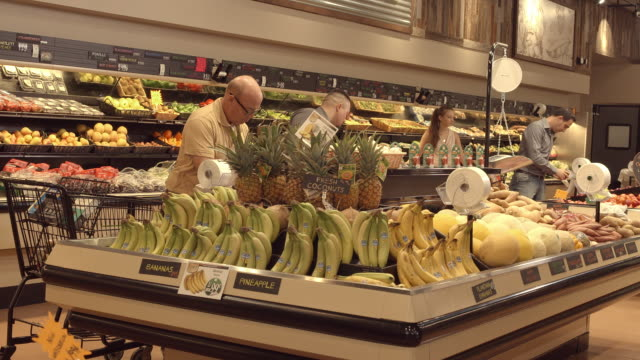 WS TD from organic locally grown sign to produce section in grocery store as customers browse fruits and vegetable items on display