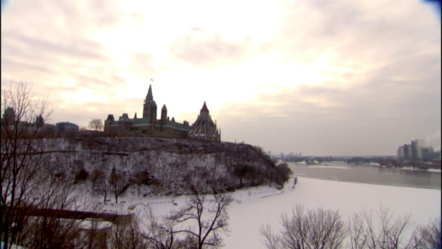 from ottawa river to buildings of parliament hill including peace tower atop snowy hill covered w/ bare trees, bright sky bg. capital, clock tower,... - parliament hill stock videos & royalty-free footage