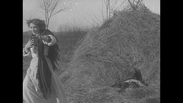 [from paramount screen savers date unknown] [actual film title not known] woman carrying young girl staggers out from behind haystack collapses at... - haystack stock videos & royalty-free footage