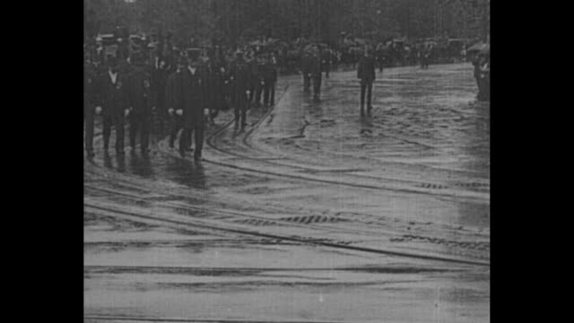 [from paramount screen souvenirs 1932] scores of soldiers with rifles marching on a wet street and dignitaries walking followed by pres william... - carro funebre video stock e b–roll