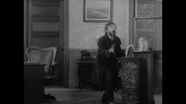 "vídeos de stock, filmes e b-roll de [from paramount screen souvenirs, 1932] [vo humorous narration throughout] title card: ""ruined!..."" / man reacts with anguish as he looks at stock... - capital letter"