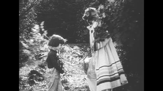[from paramount screen souvenirs collection compilation undated] woman and child both carrying leafy branches enter a forest glade woman carries... - picnic basket stock videos and b-roll footage