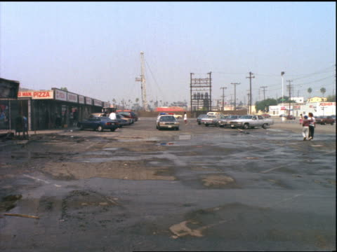 from parking lot with police cars to burnt stores in mall / los angeles riots - 1992年点の映像素材/bロール