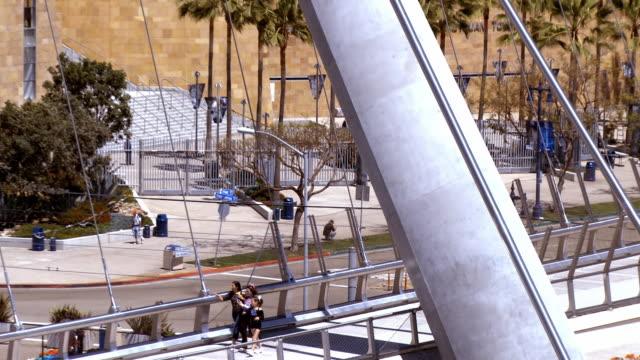 LS ZO from pedestrian crossing pedestrian bridge to WS of Petco Park baseball stadium exterior / San Diego, California, USA