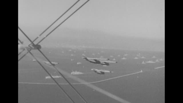 from plane of us navy planes flying in formation above ships / low angle view of planes flying in formation overhead / note: exact month/day not known - 低い点の映像素材/bロール