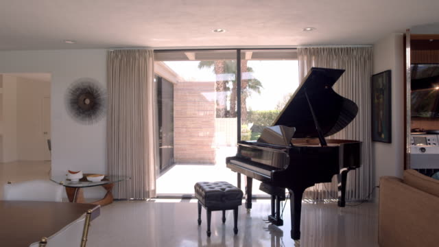 TS from planked wood ceiling to grand piano on terrazzo floor against floor-to-ceiling glass windows in Desert Modern home