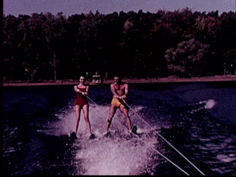 1965 ws pov from rear of boat as couple water ski in tandem/ detroit, michigan - waterskiing stock videos & royalty-free footage