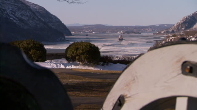 From ship on icy Hudson River BG to MS old style field cannon on display on partially snowcovered USMA campus FG NY Army