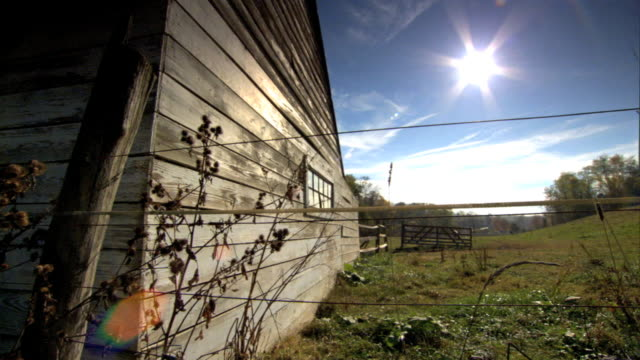 From side of barn to large field hills wooden posts fence various weeds FG BRIGHT sun glare top of frame Farm life farmland country