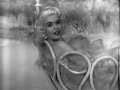 PAN from sign 'This Way to Venus' to Jayne Mansfield in bubble bath singing / TV special