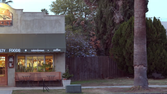 stockvideo's en b-roll-footage met pan from single family home to  neighborhood market and coffee house in historic building from 1920s / redlands, california, usa - gevel