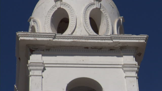 from small bell in white tower to cross atop steeple of iglesia del sagrado corazon under clear blue sky. sacred heart - steeple stock videos & royalty-free footage