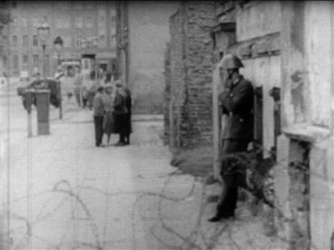 vídeos de stock e filmes b-roll de pan from soldier leaning against wall to soldiers walking by barbed wire of berlin wall - 1961