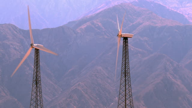 TD from spinning wind energy turbines to smoke stacks of natural gas fired electric power plant in hills above wind farm / Palm Springs, California, USA