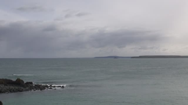 vídeos de stock e filmes b-roll de from st ives across st ives bay to the godrevey lighthouse near the town of hayle in cornwall with cutaways of surf crashing on rocks - nublado