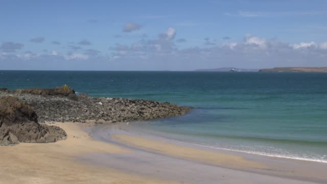 From St Ives across St Ives Bay to the Godrevey lighthouse near the town of Hayle in Cornwall With cutaways of surf on beach