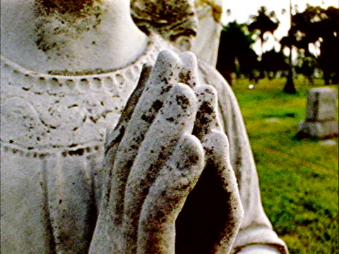 from statue of hands clasps in prayer, to face of dilapidated, worn, angel statue in unidentifiable cemetery, tombstone in distant bg . guardian,... - cemetery stock videos & royalty-free footage
