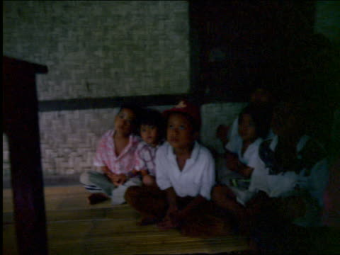 PAN from television to group of rural Asian children sitting on mat watching / Indonesia