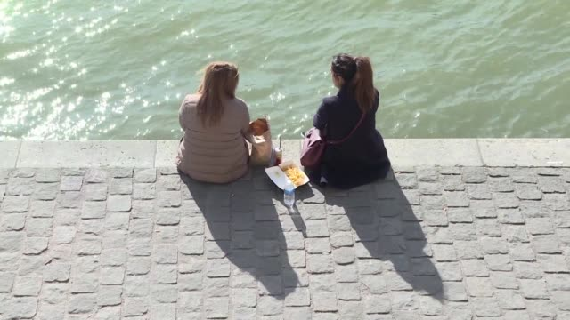 from the banks of the seine to the tuileries gardens parisians and tourists are flocking outdoors to enjoy the unusually mild weather - river seine stock videos & royalty-free footage
