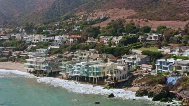 aerial from the beach in malibu towards the mountains - malibu stock videos and b-roll footage