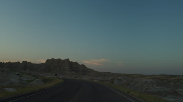 vídeos de stock e filmes b-roll de pov from the front of a vehicle traveling down a curvy two lane highway at twilight entering the dramatic rocky landscape of the badlands national monument; toward the sun on horizon. - parque nacional de badlands