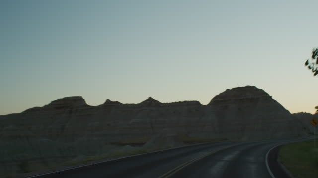 vídeos de stock e filmes b-roll de pov from the front of a vehicle traveling down a curvy two lane highway at sunset entering the dramatic rocky landscape of the badlands national monument; met by pick up truck headlights. - parque nacional de badlands
