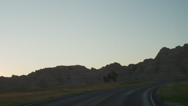 pov from the front of a vehicle traveling down a curvy two lane highway at sunset entering the dramatic rocky landscape of the badlands national monument. - badlands nationalpark stock-videos und b-roll-filmmaterial