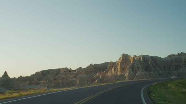 vídeos de stock e filmes b-roll de pov from the front of a vehicle traveling down a two lane highway at sunset entering the dramatic rocky landscape of the badlands national monument. - carro descapotável