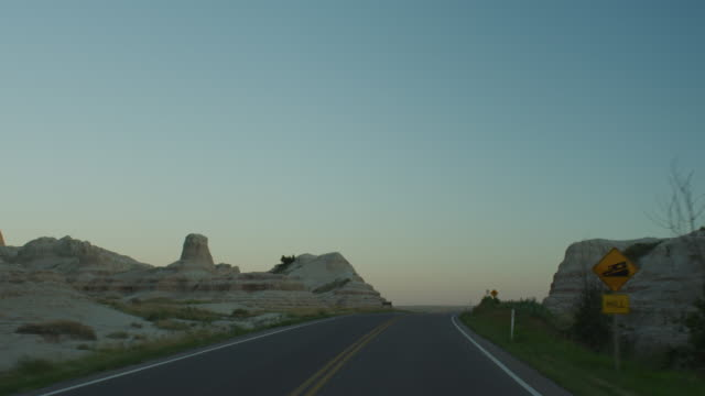 pov from the front of a vehicle traveling down a two lane highway at sunset entering the dramatic rocky landscape of the badlands national monument. - badlands nationalpark stock-videos und b-roll-filmmaterial