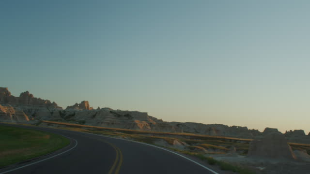 vídeos de stock e filmes b-roll de pov from the front of a vehicle traveling down a two lane highway at sunset entering the dramatic rocky landscape of the badlands national monument. - parque nacional de badlands