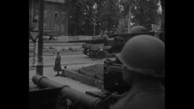 stockvideo's en b-roll-footage met vs pov from the gun turret of an american tank as it rolls though the ruins of berlin it passes a group of solemn german citizens a field gun and an... - 1945