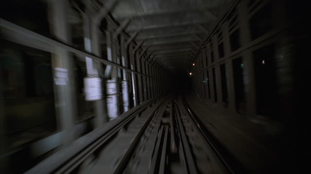 POV from the last car of a subway train passing through a narrow underground tunnel and past several platform stations.