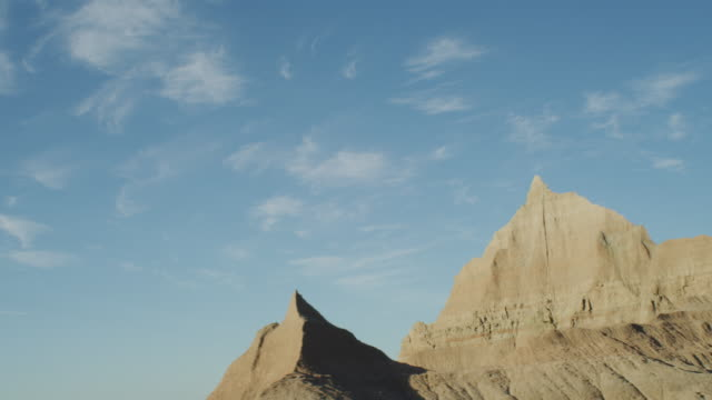 vídeos de stock e filmes b-roll de pov from the left side of a vehicle traveling down a two lane highway at sunset entering the dramatic rocky landscape of the badlands national monument; beautiful rocky formations. - parque nacional de badlands