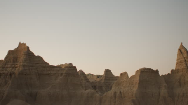 pov from the left side of a vehicle traveling down a two lane highway at sunset entering the dramatic rocky landscape of the badlands national monument; beautiful rocky formations. - badlands national park video stock e b–roll