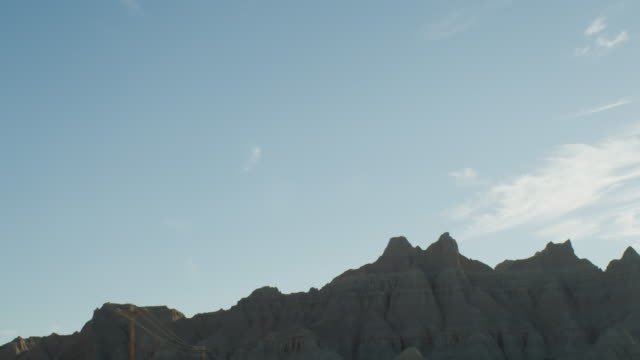 pov from the left side of a vehicle traveling down a two lane highway at sunset entering the dramatic rocky landscape of the badlands national monument; beautiful rocky formations. - badlands nationalpark stock-videos und b-roll-filmmaterial