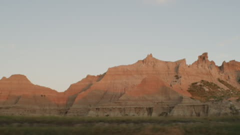 pov from the left side of a vehicle traveling down a two lane highway at sunset entering the dramatic rocky landscape of the badlands national monument; beautiful rocky formations. - badlands stock videos & royalty-free footage