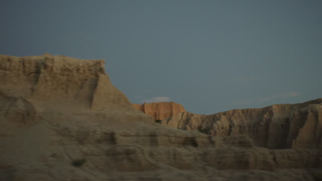 vidéos et rushes de pov from the left side of a vehicle traveling down a two lane highway at sunset entering the dramatic rocky landscape of the badlands national monument; beautiful rocky formations. - dakota du sud