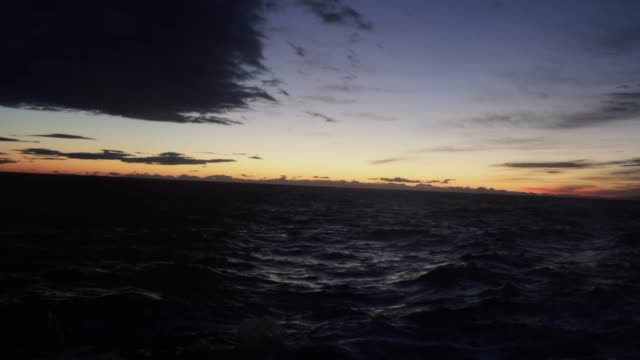 from the porthole window of a vessel: calm sunset sea - ship stock videos & royalty-free footage