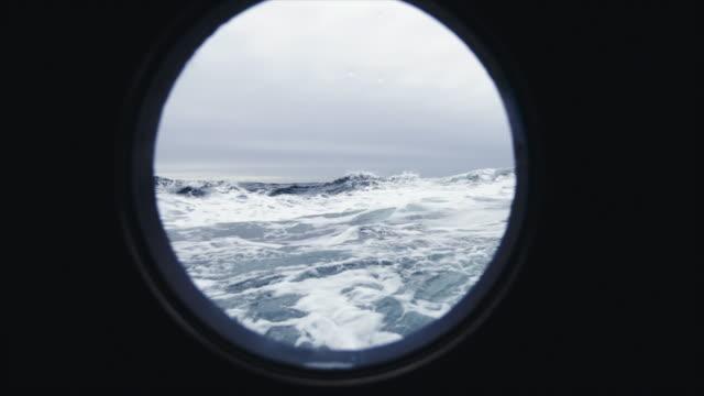 aus dem bullauge fenster eines schiffes in rauer see - kreis stock-videos und b-roll-filmmaterial