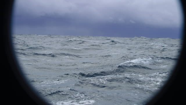 from the porthole window of a vessel in a stormy sea - mulinello video stock e b–roll