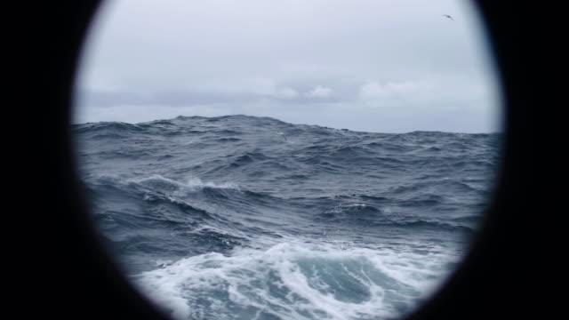 vidéos et rushes de dans la fenêtre hublot d'un navire dans une mer orageuse - hublot
