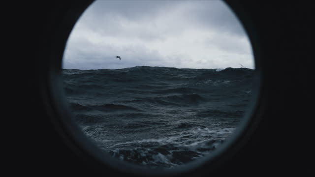 vídeos de stock e filmes b-roll de from the porthole window of a vessel in a stormy sea - barco
