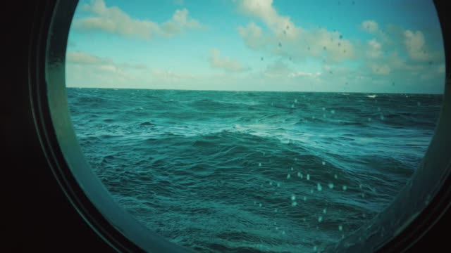 from the porthole window of a vessel in rough sea - sailboat stock videos & royalty-free footage