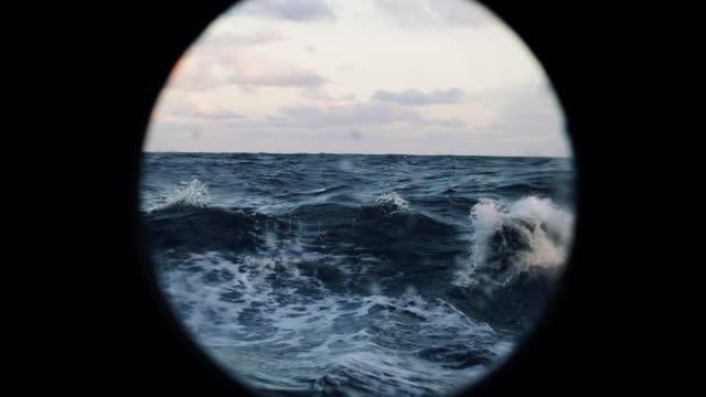 dalla finestra dell'oblò di una nave in mare agitato - barca da diporto video stock e b–roll