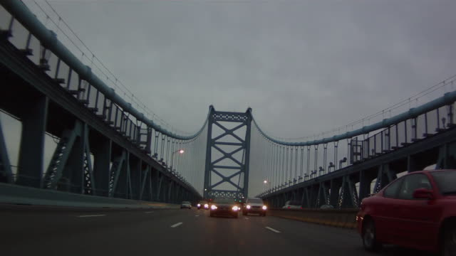 pov from the rear of a vehicle traveling across a large urban suspension bridge into a large city with moderate traffic headlights and an overcast sky. - ベンフランクリン橋点の映像素材/bロール
