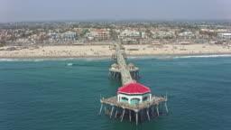 AERIAL From the sea towards the pier on the sandy beach of the Huntington Beach city, CA